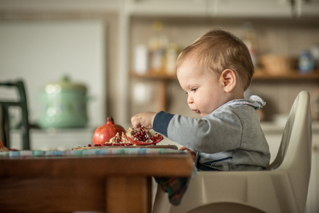 curiously: Baby eating a pomegranate fruit and curiously watching a fruit Stock Photo