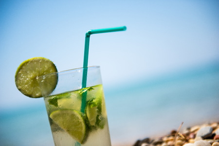 Mojito cocktail with lime and mint in highball glass on beach good as background with copy space