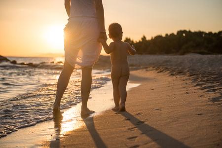 Vrouw adn haar zoon lopen op het strand in zonsondergang Stockfoto
