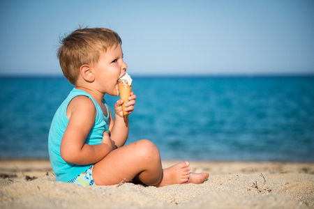 Sweet little child eating ice cream on beach, summertime Banco de Imagens
