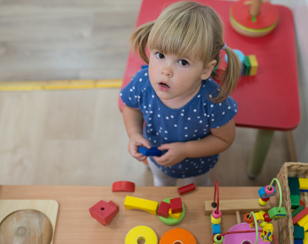 kindy: Portrait of blonde girl is playing and looking at camera