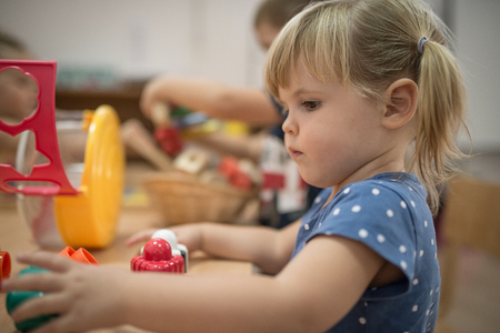 kindy: Caucasian girl is playing at kindergarten