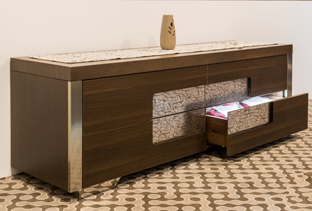 Wooden chast with open drawer in home interior