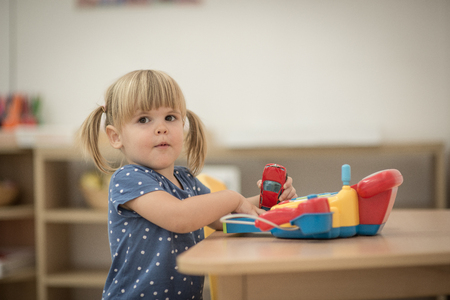 kindy: Caucasian smiling girl is playing at kindergarten