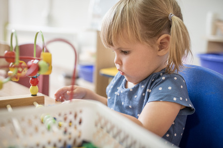 kindy: Curious little girl is plying at kindergarten