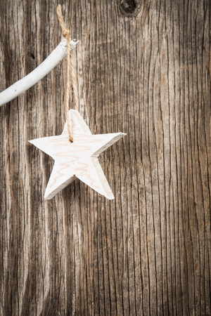 christmastide: Cgristmas star hanging on branch over wooden background