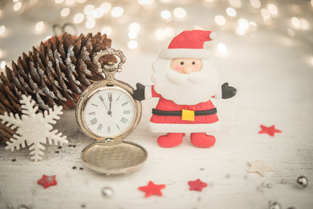 retro christmas: Ancient clock shows midnight eve and Santa Claus with stars and snowflake ornament fo Christmas