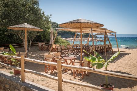 Outdoor coffee shop on sandy beach with straw parasols 版權商用圖片