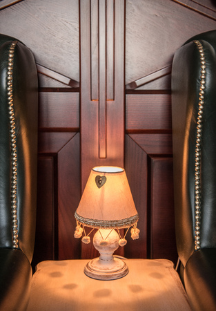 Little old fashioned lamp between luxury leather armchairs 版權商用圖片