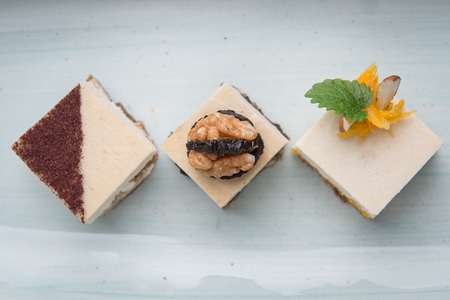 Mixed vegan raw cakes in row over white plate