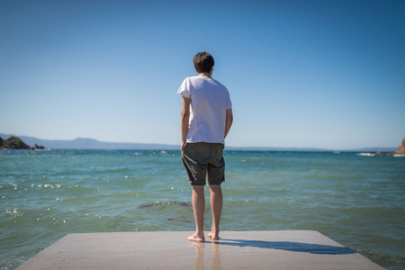 Boy standin alone on dock looking out to sea