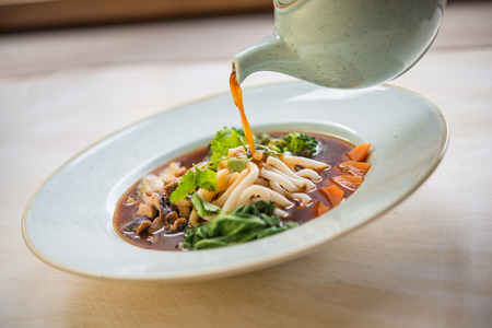 Vegan ramen with chinese cacage, udon noodle, spring onion, broccoli, shiitake and coriander 版權商用圖片