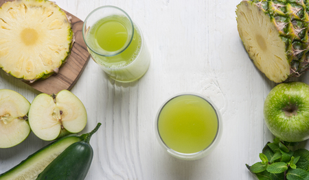 Top viev of glass juice made of cucumber, apple and pineapple