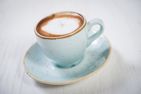 Blue cup of espresso coffee on white wooden background