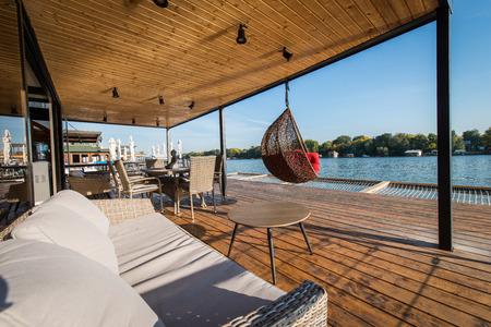 SOfa and hammock chair on terrace next to river 版權商用圖片