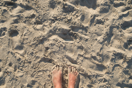 Child feet on golden sandy beach, holiday concept, top view