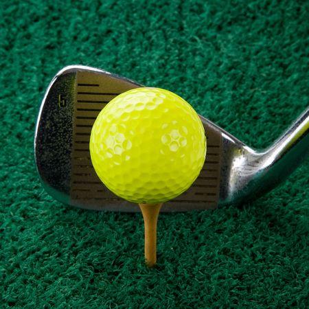 Yellow Golf Ball And Five Iron On Wood Tee