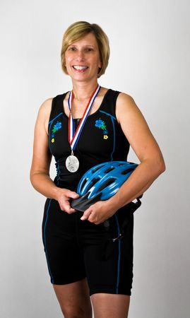 physically: Physically Fit Senior  Boomer Women with Triathlon Gear and Medal