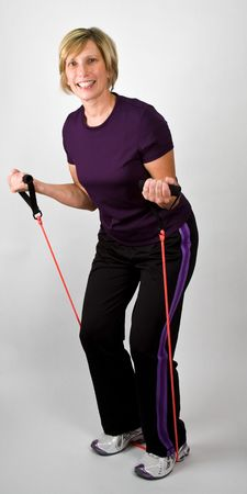 physically: Physically Fit Senior  Boomer Women Working Out With Resistance Bands