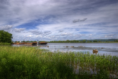 A picture of the Mississippi River with a beautiful sky and grain barge. Stock Photo - 8510155