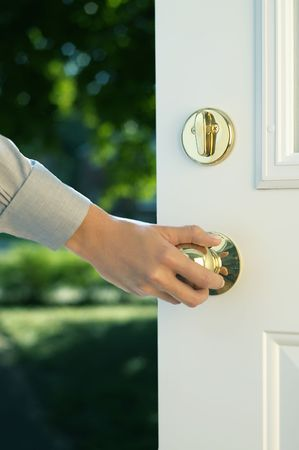 handle: Woman hand opening door Stock Photo