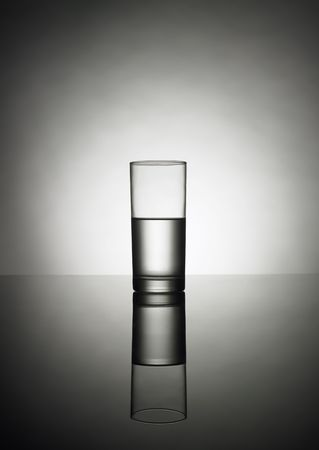 A half glass of water on a reflexion photo