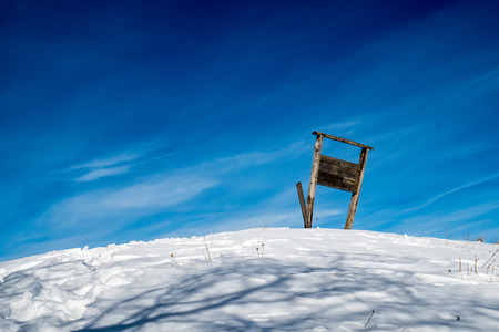 wooden sign on a snowy hill with background of blue sky