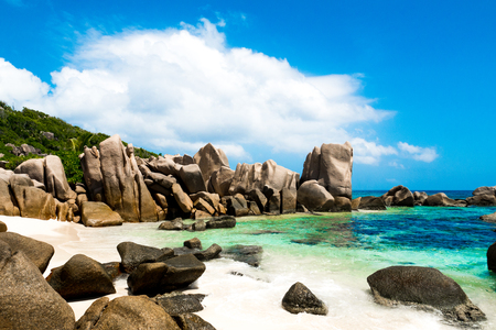 Large panorama of a tropical beach with green natural lagoon, white sand and big rocks, Indian Ocean, Anse Marron beach in La Digue, Seychelles