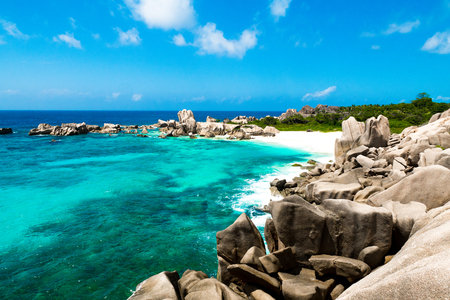 Natural and isolated tropical beach with big rocks, with sand and transparent water on a sunny day, Anse Marron, La Digue, Seychelles Stock Photo
