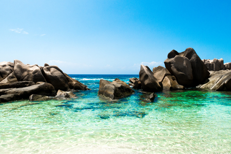 Tropical beach with natural green lagoon, white sand and big rocks, Anse Marron beach in La Digue, Seychelles