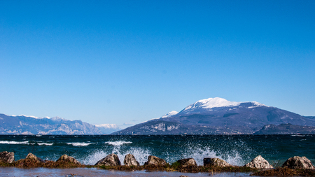 Landscape of a lake with waves and squirts on a windy day, background with alpine mountains Stock Photo