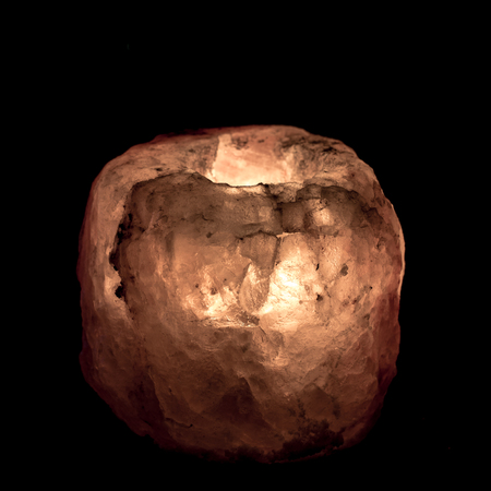 Salt lamp made with pink Himalayan salt, isolated on black background Stock Photo