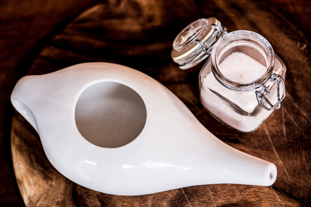 neti pot, ayurvedic tools for cleaning nose with water and salt, view from top, wooden table and board on background