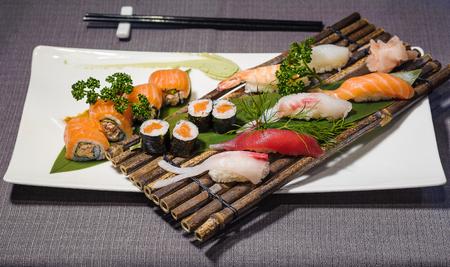Mix of different japanese traditional food, urumaki, nighiri and hosomaki, served on dish and bamboo rack