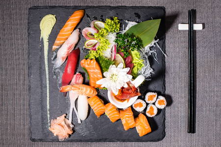 Mix of different japanese traditional food, sushi and sashimi served on a blackboard 스톡 콘텐츠