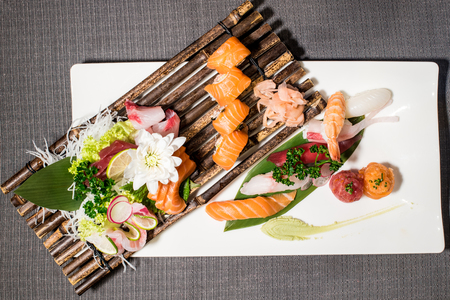 Mix of different japanese traditional food, nighiri fishes tartare and hosomaki, served on dish and bamboo rack Stock Photo