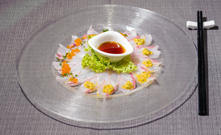 fresh amberjack carpaccio with salad and citrus fruit sauce served on a big rounded glass dish