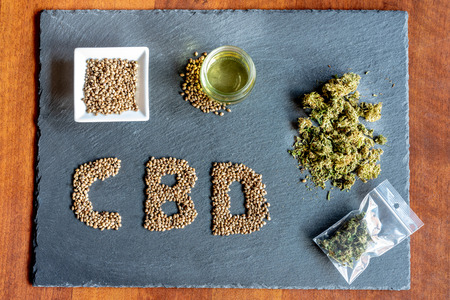 initials of the active ingredient cbd on a slate with medical marijuana sprouts, hemp seeds, essential oil Stock Photo