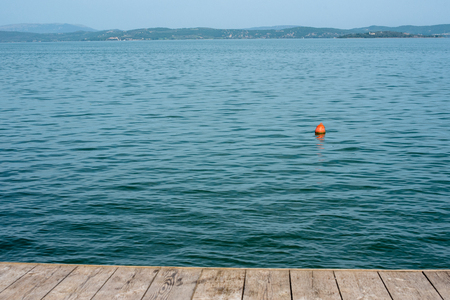 lake Trasimeno, lake landscape with a red buoy seen from a pier, Italy Stok Fotoğraf