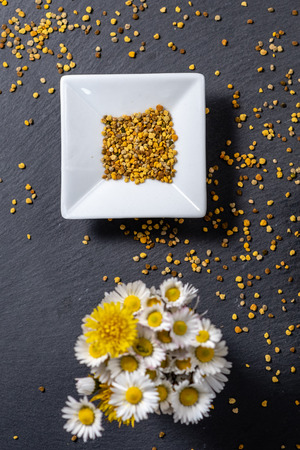 small bowl of pollen grains with small bunch of flowers out of focus, pollen on slate background Banco de Imagens