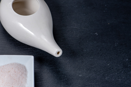 set for nasal cleaning with neti pot, ayurvedic medicine system on a black slate, top view, with hymalaian salt Stock Photo