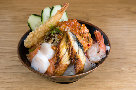 typical Japanese fish donburi, shrimp tempura, raw shrimps, salmon fillets, grilled tuna, caviar, tuna tartare, sliced cucumbers, raw sea bass fillets, omelette and different types of caviar, on a wooden table