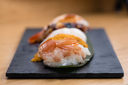 detail of steamed prawn nigiri, with background of nigiri with Pacific Sea Urchin, steamed salmon, steamed shrimp, caviar, roasted eel and squid, wooden table background