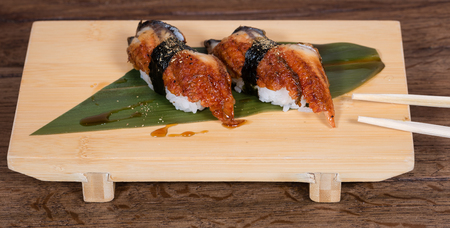 nigiri of roasted eel, tied to the rice ball with a seaweed, close up, on a wooden plate with chopsticks