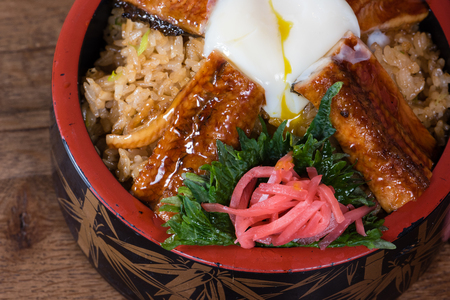 Japanese fusion dish with spicy rice with tamari sauce, roasted eel, egg and red turnip, in a decorated bowl, dark wood table background, details