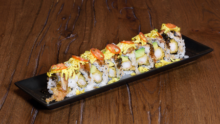 special sushi roll with roasted eel, shrimp in tempura, cherry tomatoes, mayonnaise, omelette and sesame, dark wood table background Reklamní fotografie