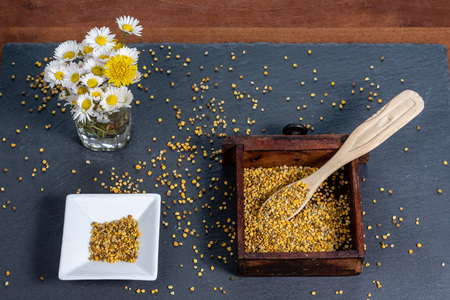 photo composed of a square bowl of white ceramic, a wooden box full of pollen grains of bees and a bunch of daisies, on a slate board, top view