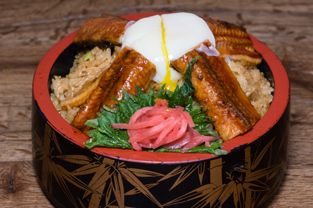 Japanese fusion dish with spicy rice with tamari sauce, roasted eel, egg and red turnip, in a decorated bowl, dark wood table background