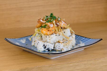 pyramid of maki roll with fried shrimps, tempura vegetables, sesame and rocket decoration on a plate with cheese cream 版權商用圖片