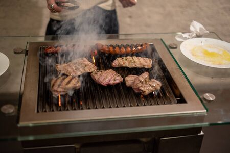 different types of meat, beef steaks and pork sausages, cooked on a grill indoor Stock Photo
